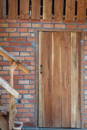 non urban: wood door on brick wall of house Stock Photo
