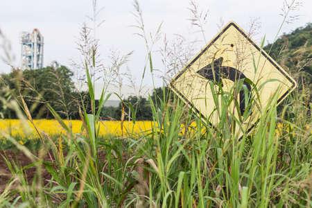 turn left: erba overlay segnali stradali girare sullo sfondo a sinistra e la fabbrica