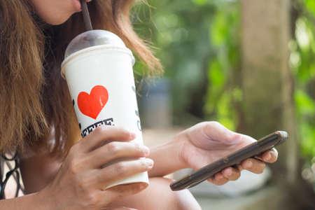vrouwen drinken ijskoffie en het gebruik van slimme telefoon mobiele outdoor