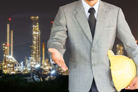 businessman with handshake to cooperation and oil refinery night background