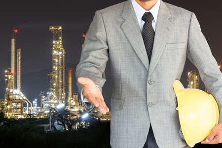 zakenman met handdruk om de samenwerking en olieraffinaderij nacht achtergrond