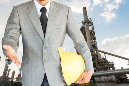 businessman with handshake to cooperation and oil refinery factory background photo