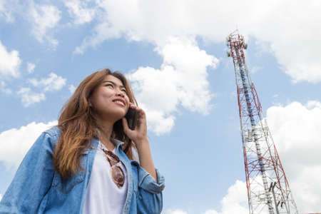 beauty women use smart phone call and satellite communication tower background photo
