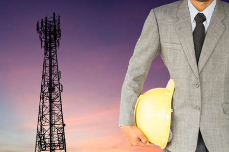 telecoms: businessman engineer and telecommunication tower at sunset background
