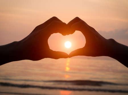 paar handen hart liefde bij zonsondergang op het strand, valentijnsdag