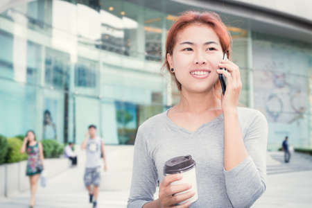 telecoms: beautiful young women call phone and hold coffee cup urban background