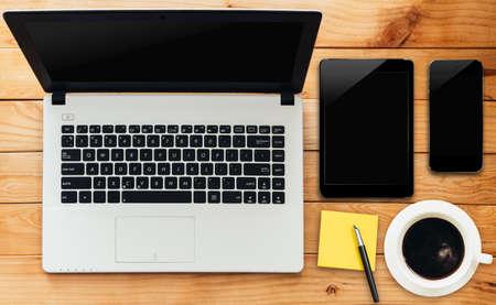 laptop computer tablet telefoon en koffie drinken op hout werkruimte