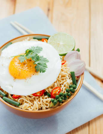 instant noodle: noodle and fried egg in bowl asia culture food Stock Photo