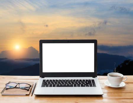 laptop computer en de koffie op houten werkruimte en de bergen bij zonsondergang op de achtergrond Stockfoto