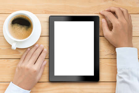 wood work: business man using tablet white screen display with coffee drink on wood desk