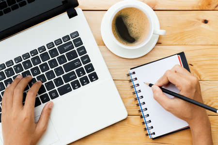 hand using laptop and write note inspire idea on wood desk