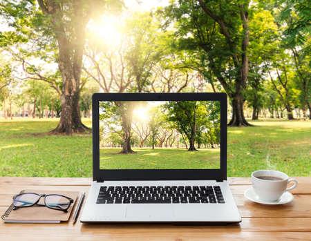 exteriores: ordenador portátil y el café en la área de trabajo de la madera y el fondo del parque