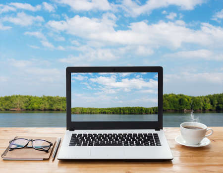 laptop computer and coffee on wood workspace and mangrove forest background Stock Photo