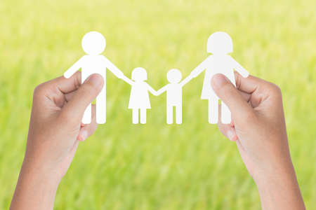 planificacion familiar: modelo de familia asimiento de la mano sobre fondo verde Foto de archivo
