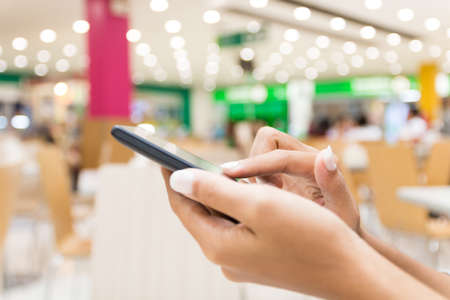 lady on phone: closeup hand using smart phone in department store urban lifestyle Stock Photo