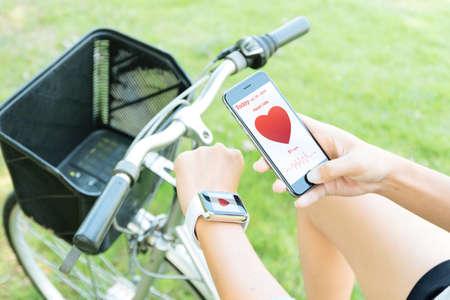 vrouw hand met behulp van de telefoon en kijken naar een gezonde toepassing op de sport uit te oefenen Stockfoto