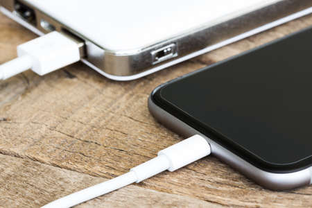 charging: closeup phone charging white power bank portable devie Stock Photo