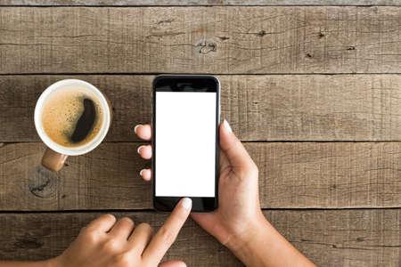 taza cafe: mano con la pantalla en blanco de teléfono en la vista superior Foto de archivo