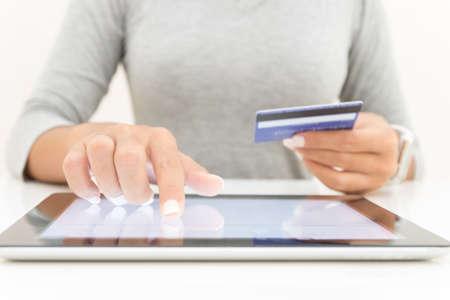女性を tablet とクレジット カードを使用して支払うオンライン ショッピング