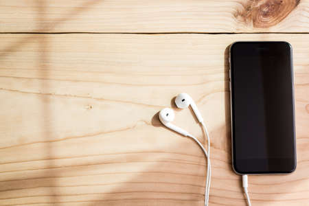 phone and headphone on wood background Stok Fotoğraf - 47692775