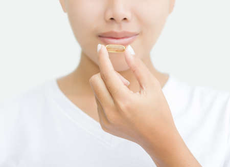 vitamins pills: close up woman taking vitamin capsule for healthy