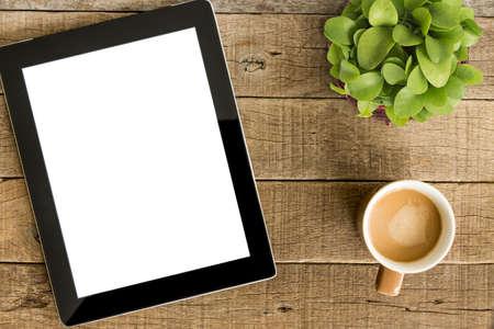 白い画面表示と木製のテーブルの上のコーヒーをタブレットします。