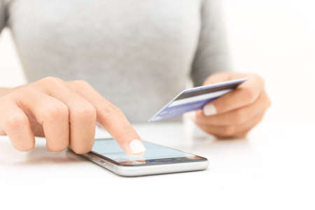closeup woman hand using phone and credit card shopping online