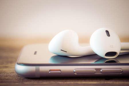 manzana: auriculares modernos de detalle sobre los medios de comunicación del teléfono portátil Foto de archivo