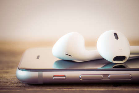 apple: closeup modern headphone on phone media portable