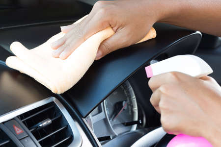 closeup hand cleansing car dashboard Stock Photo