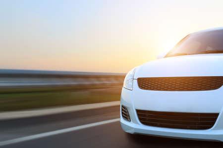 carro: la velocidad de movimiento del automóvil en el asfalto al atardecer Foto de archivo