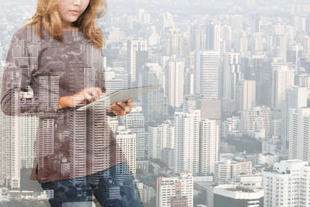 abstract building: double exposure of woman using tablet technology and urban building background Stock Photo