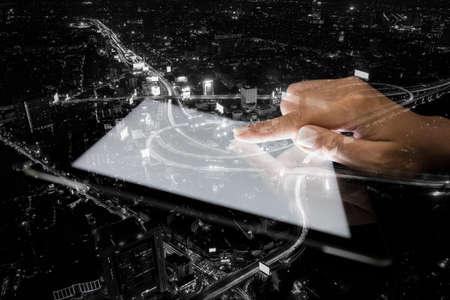 exposicion: doble de la mano de la exposición que usa la tableta y la ciudad en el fondo la noche