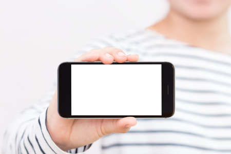 telecom: woman holding phone white screen selective focus on hand showing Stock Photo