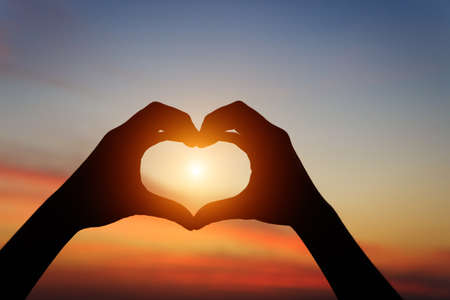 silhouette hand gesture feeling love during sunset