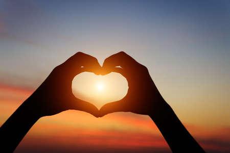 silueta de la mano gesto de sentir el amor durante el atardecer