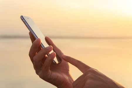 closeup hand using phone during at sunset