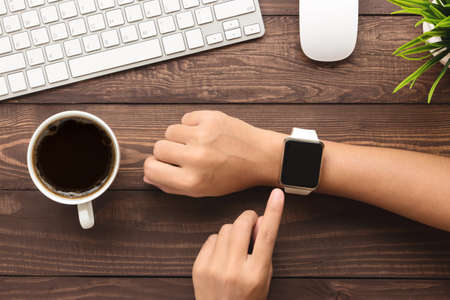 hand using smartwatch on desk top view Stok Fotoğraf - 56530744