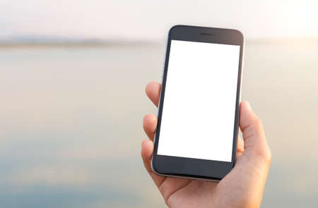 mobile devices: hand holing phone white screen at outdoor lifestyle