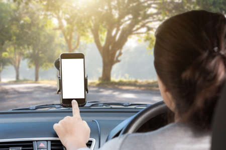 woman use phone mount to glass in car on rural road