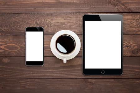 telefoon tablet en een koffiekopje op houten tafelblad bekijken Stockfoto