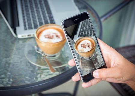 close-up hand nemen foto koffie op werktafel