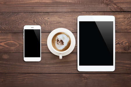 top seven: white phone tablet and coffee cup on wood table top view Stock Photo