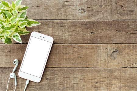 Telefoon leeg wit scherm op oude houten tafel, mockup telefoon rose gouden kleur Stockfoto - 64262340