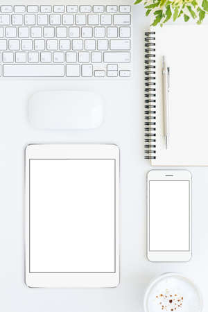 top seven: phone and tablet blank screen on white table format vertical top view