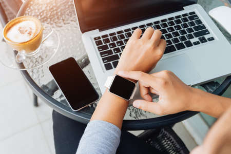 woman using smart watch in coffee shop, modern city lifestyle Stock Photo
