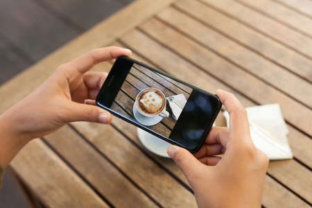 top seven: close-up hand holding phone mobile taking photo coffee on table