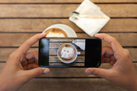 close-up hand holding phone taking coffee photo on table Standard-Bild