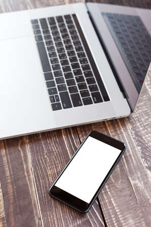 pro: mobile and laptop on wood desk selective focus on phone white blank screen vertical view Stock Photo
