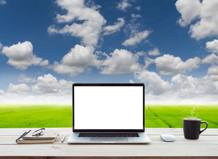 laptop computer showing white screen on work table meadow and blue sky view background Stok Fotoğraf